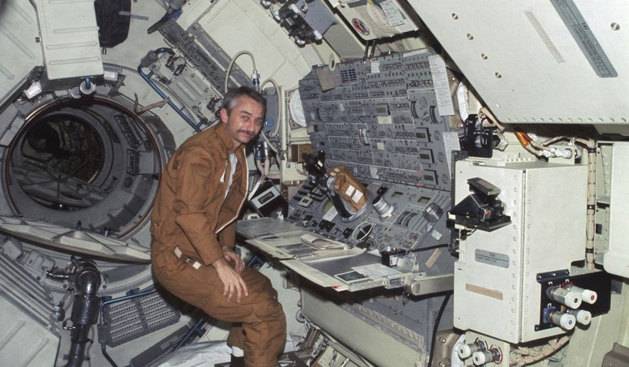 In this 1973 photo made available by NASA, astronaut Owen K. Garriott floats in front of the Apollo Telescope Mount console in the Multiple Docking Adapter of the Skylab space station in Earth orbit. The space agency said Garriott died at his home in Huntsville, Ala., on Monday, April 15. 2019. He was 88. (NASA via AP)