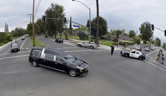 The hearse carrying the body of California Highway Patrol Sgt. Steve Licon makes its way through the intersection of Madison Street and Magnolia Avenue in Riverside, Calif., Tuesday morning, April 16, 2019. The 53-year-old Licon was fatally hit by a car on April 6 after he had pulled someone over for speeding on Interstate 15 in Lake Elsinore. Michael Joseph Callahan of Winchester was arrested and charged with second-degree murder in Licon's death. (Will Lester/The Orange County Register via AP)