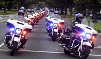 The funeral procession for California Highway Patrol Sgt. Steve Licon makes its way through the intersection of Madison Street and Magnolia Avenue in Riverside, Calif., Tuesday morning, April 16, 2019. The 53-year-old Licon was fatally hit by a car on April 6 after he had pulled someone over for speeding on Interstate 15 in Lake Elsinore. Michael Joseph Callahan of Winchester was arrested and charged with second-degree murder in Licon's death. (Will Lester/The Orange County Register via AP)