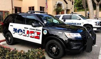 This undated photo provided by the Laguna Beach Police Department shows their newly decorated Police SUV patrol vehicles in Laguna Beach, Calif. An American flag graphic on the side of freshly painted police cars is dividing a small coastal city in Southern California. Some people in Laguna Beach feel the flag design is too aggressive while others are astonished that anyone would object to the American flag, The Los Angeles Times reported Saturday, April 13, 2019. (Laguna Beach Police Department via AP)