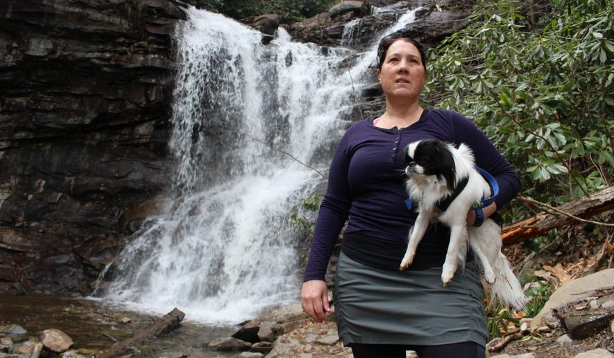 Jacqueline Zito poses for a portrait with her dog, Sally, at the base of Glen Onoko Falls in Jim Thorpe, Pa., Tuesday, April 16, 2019. Zito and other hikers are opposed to a Pennsylvania Game Commission plan to shut down the popular falls trail over safety concerns. Pennsylvania officials are closing one of the most scenic and popular hiking trails in the state because of longstanding concerns about its safety, prompting backlash from hikers. (AP Photo/Michael Rubinkam)