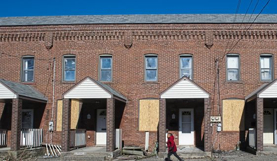 A child runs past a line of boarded up row homes on Tuesday, March 26, 2019, in Duquesne. Duquesne, home to slightly more than 5,500 residents, is one of seven Allegheny County municipalities in which half of or more of the kids live in poverty. (Stephanie Strasburg/Post-Gazette via AP)