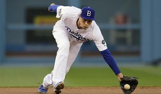 Los Angeles Dodgers shortstop Corey Seager fields a ball hit by Cincinnati Reds' Curt Casali during the first inning of a baseball game, Monday, April 15, 2019, in Los Angeles. Casali was thrown out at first on the play. (AP Photo/Mark J. Terrill)