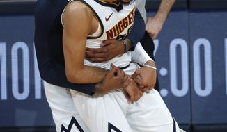 Denver Nuggets forward Torrey Craig, back, hugs guard Jamal Murray after he hit a key basket late in the second half of Game 2 of an NBA basketball playoff series against the San Antonio Spurs, Tuesday, April 16, 2019, in Denver. The Nuggets won 114-105. (AP Photo/David Zalubowski)