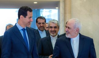 """This photo released on the official Facebook page of Syrian Presidency shows Syrian President Bashar Assad, left, speaking with Iranian Foreign Minister Mohammad Javad Zarif, right, in Damascus, Syria, Tuesday, April 16, 2019. Zarif has blasted upon arrival in Syria the Trump administration decision to designate Tehran's Revolutionary Guards Corps a terrorist organization calling it a """"stupid act."""" (Syrian Presidency Facebook page via AP)"""
