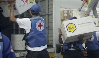 In this image taken from video provided by the International Red Cross, volunteers load into waiting vehicles the first shipment of humanitarian aid from the International Federation of Red Cross and Red Crescent Societies at the Simon Bolivar International Airport in Maiquetia, Venezuela, Tuesday, April 16, 2019. The Red Cross announced in late March that it had obtained permission from officials to begin delivering assistance to the crisis-stricken country. (International Committee of the Red Cross via AP)