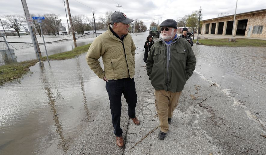 2020 Democratic presidential candidate Washington Gov. Jay Inslee, left, talks with climate analyst John Davis, of Hamburg, Iowa, while touring flood damage, Friday, April 12, 2019, in Hamburg, Iowa. (AP Photo/Charlie Neibergall)