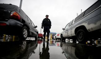 In this Dec. 3, 2014, file picture, an Immigration and Customs Enforcement (ICE) agent watches cars as they wait to enter the United States from Tijuana, Mexico, through the San Ysidro port of entry in San Diego. (AP Photo/Gregory Bull) ** FILE **