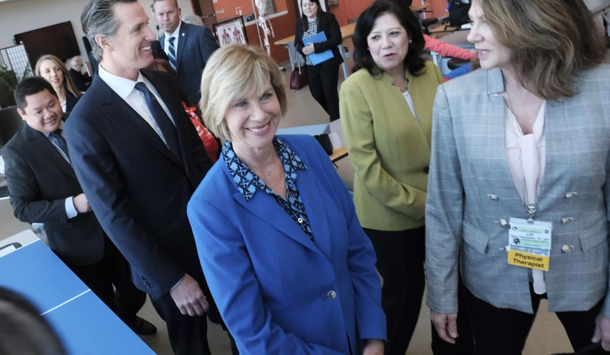 Led by Physical Therapist Mary Thompson, right, Los Angeles County Board of Supervisors Janice Hahn, center and California Governor Gavin Newsom, left and L.A. County Supervisor Hilda Solis, second from right, take a tour of the the Rancho Los Amigos National Rehabilitation Center in Downey, Calif. on Wednesday, April 17,2019. (AP Photo/Richard Vogel)