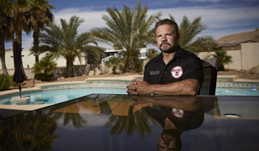 In this April 9, 2019, photo, Grant Whitus poses for a portrait at his home in Lake Havasu City, Ariz. Whitus' marriage fell apart a year after he led his SWAT team into Columbine High School's library, where he was the first to find the dead children's bodies. (AP Photo/John Locher)