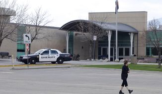 """A woman walks across an empty parking lot a Columbine High School, Wednesday, April 17, 2019, in Littleton, Colo., where two student killed 12 classmates and a teacher in 1999. The school was closed along with hundreds of others in Colorado after an armed young Florida woman who was allegedly """"infatuated"""" with Columbine threatened violence just days ahead of the 20th anniversary of the attack. (AP Photo/Joe Mahoney)"""