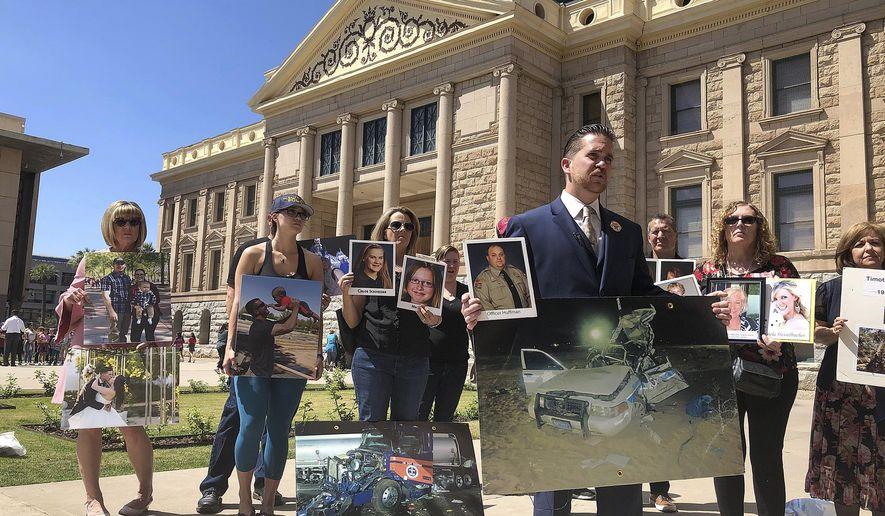 Brendan Lyons, director of the group Look! Save a Life, foreground, stands with relatives of people who have been killed by distracted drivers at the state Capitol in Phoenix on Wednesday, April 17, 2019. Arizona House lawmakers will get to choose between three proposed laws that are designed to deal with distracted driving caused by cell phone use, Speaker Rusty Bowers announced after a closed-door meeting of majority Republicans Wednesday. (AP Photo/Jonathan J. Cooper)