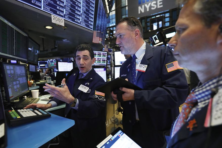 FILE - In this April 12, 2019, file photo specialist Peter Mazza, left, and trader Jonathan Corpina, center, work on the floor of the New York Stock Exchange. The U.S. stock market opens at 9:30 a.m. EDT on Wednesday, April 17. (AP Photo/Richard Drew, File)