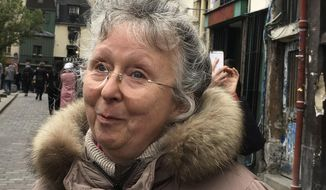 Cecile Deleville smiles during an interview with the Associated Press in Paris Tuesday April 16, 2019. For the 66-year-old Deleville, there is no replacement for Notre Dame, where she worshipped regularly, sometimes daily, for two decades. She said it's likely she would go to the nearby Left Bank church Saint Severin, which she had just exited before sharing her feelings. (AP Photo/Elaine Ganley)