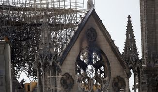A worker checks on a wooden support structure placed on the Notre Dame Cathedral in Paris, Wednesday, April 17, 2019. Nearly $1 billion has already poured in from ordinary worshippers and high-powered magnates around the world to restore Notre Dame Cathedral in Paris after a massive fire. (AP Photo/Francois Mori)