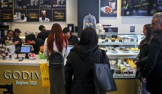 Customers wait in line for service at Godiva's new cafe in New York, Tuesday April 16, 2019. Godiva, the private Belgium chocolate maker, is looking beyond its iconic gold gift box of chocolates. The confectioner is rolling out 2,000 cafes that will serve a complete menu of items like the croiffle, a croissant and waffle hybrid. (AP Photo/Bebeto Matthews)
