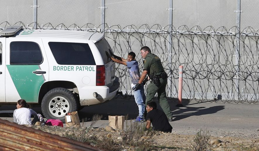 In this Dec. 15, 2018, file photo, Honduran asylum seekers are taken into custody by U.S. Border Patrol agents after the group crossed the U.S. border wall into San Diego, Calif., seen from Tijuana, Mexico. Facing high turnover, the Border Patrol is instituting a 5% retention bonus in the fall of 2019 to incentivize agents to remain with the service. (AP Photo/Moises Castillo, File) **FILE**
