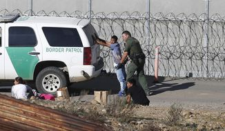 """FILE - In this Dec. 15, 2018, file photo, Honduran asylum seekers are taken into custody by U.S. Border Patrol agents after the group crossed the U.S. border wall into San Diego, Calif., seen from Tijuana, Mexico. Detained asylum seekers who have shown they have a credible fear of returning to their country will no longer be able to ask a judge to grant them bond. U.S. Attorney General William Barr decided Tuesday, April 16, 2019, that asylum seekers who clear a """"credible fear"""" interview and are facing removal don't have the right to be released on bond while their cases are pending and will have to wait in detention until their case is adjudicated.  (AP Photo/Moises Castillo, File)"""