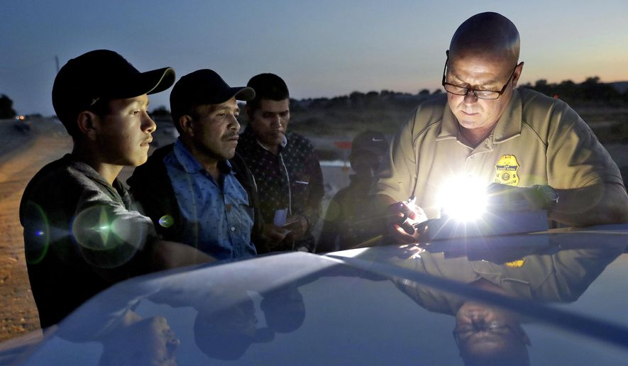 A U.S. Customs and Border Patrol agent gathers information on four Guatemalan nationals, including two men and a pair of 12 and 13-year-old boys in Yuma, Ariz. Yuma Mayor Douglas Nicholls has declared a state of emergency to deal with the number of families being released from Border Patrol custody into the city. Nicholls said Tuesday, April 16, 2019, that he had hoped not to get to this point but that the organizations helping immigrant families just don't have the capacity to deal with so many. (AP Photo/Matt York) **FILE**
