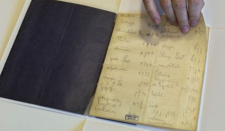 FILE -  In this file photo taken on Oct. 5, 2014, a library official shows celebrated author Franz Kafka's Hebrew vocabulary notebook at Israel's National Library in Jerusalem. A long-hidden trove of unpublished works by Franz Kafka could soon be revealed following a decade-long battle over his literary estate that has drawn comparisons to some of his surreal tales. (AP Photo/Sebastian Scheiner, File)