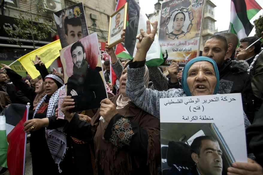 """Relatives of Palestinians held in Israeli jails hold their portraits during a protest to mark """"Prisoners Day"""" in the West Bank city of Ramallah, Wednesday, April 7, 2019.(AP Photo/Majdi Mohammed)"""