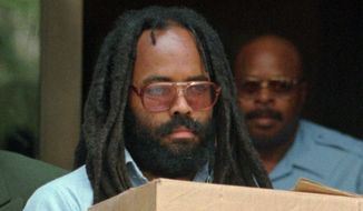 FILE - In this July 12, 1995 file photo, Mumia Abu-Jamal leaves Philadelphia's City Hall after a hearing.   The former Black Panther and death-row activist convicted of killing a Philadelphia police officer will get a new appeals hearing after the city prosecutor dropped his opposition to it. Abu-Jamal is serving a life sentence after spending decades on death row in the 1981 slaying of Officer Daniel Faulkner during a traffic stop. A city judge granted him a new hearing in December 2019 after the U.S. Supreme Court said a former Pennsylvania justice who heard his appeal had a potential conflict of interest in a similar case.(AP Photo/Chris Gardner, File)