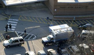 In this Dec. 14, 2012, aerial file photo, officials stand outside of Sandy Hook Elementary School in Newtown, Conn., where gunman Adam Lanza opened fire inside school killing 20 first-graders and six educators at the school. A Connecticut appeals court is scheduled to hear arguments on Wednesday, April 17, 2019, on whether parents of some of the shooting victims can sue the town for school officials' alleged failure to follow security protocols once the shooting began. (AP Photo/Julio Cortez, File)