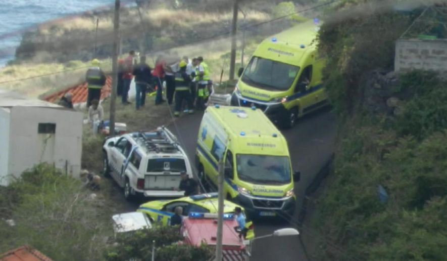 In this image from video, emergency services attend the scene after a tour bus crashed at Canico, on Portugal's Madeira Island, Wednesday April 17, 2019.  Some 28 people are reported to have died in the crash, most of them German tourists, local mayor Filipe Sousa told TV news. (TVI via AP)