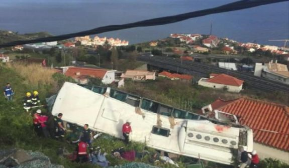 In this image from video, emergency services attend the scene after a tour bus crashed at Canico, on Portugal's Madeira Island, Wednesday, April 17, 2019. Some 28 people are reported to have died in the crash, most of them German tourists, local mayor Filipe Sousa told TV news. (TVI via AP)