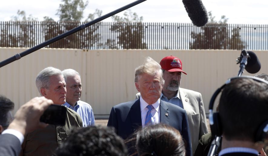 FILE - In this April 5, 2019, file photo, President Donald Trump visits a new section of the border wall with Mexico in Calexico, Calif. When Trump insisted last year that the border was in crisis, his warnings landed with a thud. Now, as the situation at the border has deteriorated to a level of alarm, Trump is again being met with skepticism, even as members on both sides of the aisle agree that there is a legitimate humanitarian emergency, with federal authorities and non-profits unable to cope with the influx of tens of thousands of Central American families seeking refuge in the U.S. (AP Photo/Jacquelyn Martin, File)