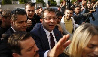 Ekrem Imamoglu, centre, of the opposition Republican People's Party (CHP) mayoral candidate in Istanbul, arrives to receive a certificate confirming his win by a slim margin against ruling party's candidate Binali Yildirim, in Istanbul, Turkey, Wednesday, April 17, 2019. Authorities have confirmed that Imamoglu won the mayoral election in Istanbul, ending nearly three weeks of recounts, although Turkey's top electoral body, has yet to consider a ruling party request for the vote in Istanbul to be invalidated. (AP Photo/Emrah Gurel)