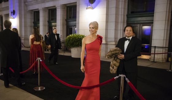In this Thursday, Jan. 19, 2017 file photo, President-elect Donald Trump adviser Kellyanne Conway, center, accompanied by her husband, George, speaks with members of the media as they arrive for a dinner at Union Station in Washington, the day before Trump's inauguration. (AP Photo/Matt Rourke)