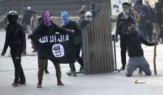 A Kashmiri protester shows Islamic state flag as others clash with Indian policemen during a protest in Srinagar, Indian controlled Kashmir, Friday, Dec. 7, 2018. Government forces fired pellet guns on Kashmiris who gathered after Friday afternoon prayers protesting against Indian rule in the disputed region. (AP Photo/ Dar Yasin)