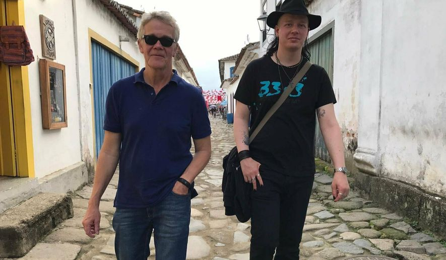 """This photo courtesy of Dag Gustafsson, taken by his wife Görel Bini Gustafsson, shows Dag with his son Ola Bini in Paraty, Brazil on May 28, 2017. Bini, a privacy activist who was detained in Ecuador shortly after Julian Assange was arrested in London, said in a statement provided by his attorney that he's being held under """"the best of circumstances"""" but that prison conditions are """"despicable."""" Ecuadorian President Lenin Moreno claims Bini hacked cellphones and online accounts belonging to private citizens and Ecuador's government. (Dag Gustafsson via AP)"""