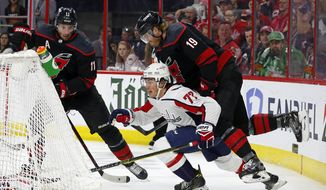 Washington Capitals' T.J. Oshie (77) battles behind the net with Carolina Hurricanes' Dougie Hamilton (19) and Jordan Staal (11) during the first period of Game 4 of an NHL hockey first-round playoff series in Raleigh, N.C, Thursday, April 18, 2019, (AP Photo/Karl B DeBlaker)