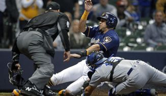 Milwaukee Brewers' Hernan Perez is tagged out at home by Los Angeles Dodgers' Austin Barnes during the eighth inning of a baseball game Thursday, April 18, 2019, in Milwaukee. (AP Photo/Aaron Gash)