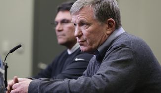 Carolina Panthers general manager Marty Hurney, front, speaks to the media as head coach Ron Rivera, back, listens in Charlotte, N.C., Wednesday, April 17, 2019 in advance of the NFL draft. (AP Photo/Chuck Burton)