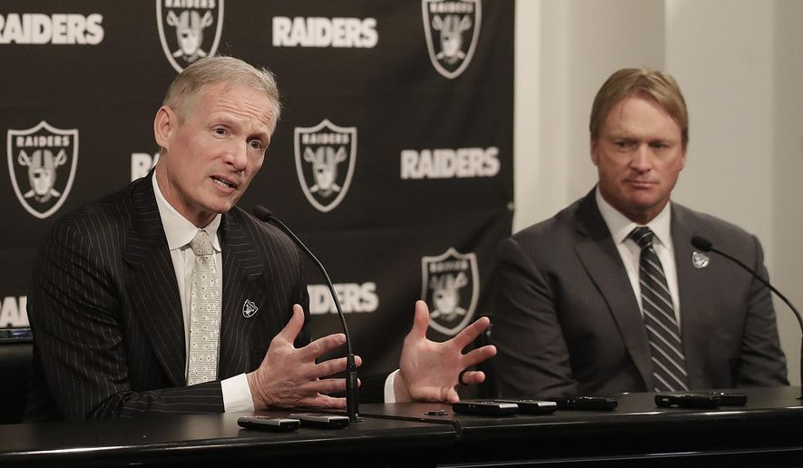 FILE - In this Monday, Dec. 31, 2018, file photo, Mike Mayock, left, speaks as Oakland Raiders head coach Jon Gruden listens at a news conference announcing Mayock as the general manager at the team's headquarters in Oakland, Calif. Mayock knows he will be highly scrutinized with three first-round picks thanks to Gruden's much-criticized trades. (AP Photo/Jeff Chiu, File)