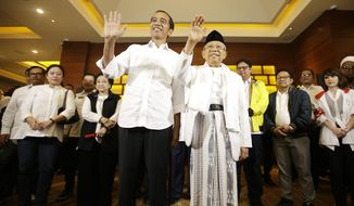 Indonesian President Joko Widodo, left, and his running mate Ma'ruf Amin wave to journalists after a press conference in Jakarta, Indonesia, Wednesday, April 17, 2019. Widodo is on track to win a second term, preliminary election results showed Wednesday, in apparent victory for moderation over the ultra-nationalistic rhetoric of his rival Prabowo Subianto. (AP Photo/Achmad Ibrahim)