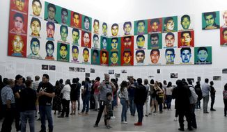 "People stand under the portraits of 43 college students who went missing in 2014 in an apparent massacre, by Chinese concept artist and government critic Ai Weiwei at the Contemporary Art University Museum (MUAC ) in Mexico City, Mexico, Saturday, April 13, 2019. Each portrait in the work of art titled ""Reestablish Memories"" is made out of lego blocks. (AP Photo/Claudio Cruz)"