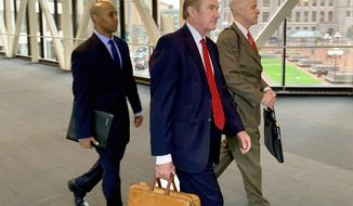 Former Minneapolis police officer Mohamed Noor, left, arrived with his defense attorneys Peter Wold, center, and Thomas Plunkett, right, on April 17, 2019, before another day of testimony in Noor's murder and manslaughter trial in Minneapolis. Noor is accused of fatally shooting an unarmed woman, Justine Ruszczyk Damond, on July 15, 2017, after she called 911 to report a possible sexual assault near her home. (AP Photo/Jeff Baenen)