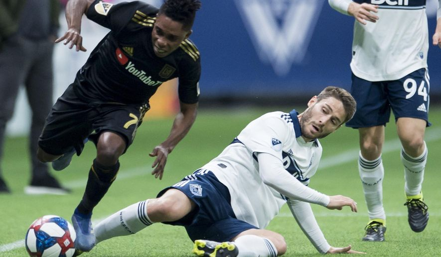 Vancouver Whitecaps midfielder Ion Erice, lower right, fights for control of the ball with Los Angeles FC forward Latif Blessing (7) during the first half of an MLS soccer match Wednesday, April 17, 2019, in Vancouver, British Columbia. (Jonathan Hayward/The Canadian Press via AP)