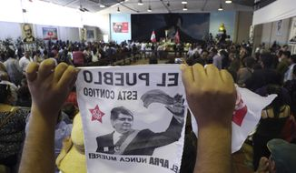 A supporter holds up an image of Peru's late President Alan Garcia on the second day of his wake at his party's headquarters in Lima, Peru, Thursday, April 18, 2019. Garcia shot himself in the head and died Wednesday as officers waited to arrest him in a massive graft probe that has put the country's most prominent politicians behind bars and provoked a reckoning over corruption. (AP Photo/Martin Mejia)