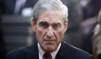 In this Oct. 28, 2013, file photo, former FBI Director Robert Mueller is seated at FBI Headquarters in Washington. (AP Photo/Charles Dharapak, File)