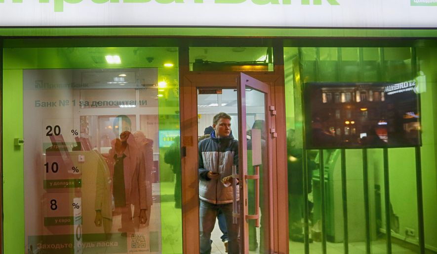 FILE - In this file photo taken on Monday, Dec. 19, 2016, a client leaves PrivatBank as other clients take money from PrivatBank's cash machine in Kiev, Ukraine. A Ukrainian court has ruled that the 2016 nationalization of the major bank PrivatBank, owned by a powerful tycoon Ihor Kolomoyskyi, was illegal. (AP Photo/Efrem Lukatsky, File)
