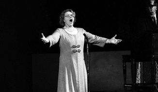 """FILE - In this May 13, 1975, file photo, Kate Smith sings """"God Bless America"""" before an NHL hockey Stanley Cup playoff game between the New York Islanders and the Philadelphia Flyers in Philadelphia. The New York Yankees have suspended the use of Smith's recording of """"God Bless America"""" during the seventh-inning stretch while they investigate an allegation of racism against the singer. (AP Photo, File)"""