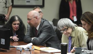 David Turpin, second from right, and wife, Louise, left, sit in a courtroom during their sentencing hearing Friday, April 19, 2019, in Riverside, Calif. The California couple who pleaded guilty to years of torture and abuse of 12 of their 13 children have been sentenced to life in prison with possibility of parole after 25 years. (Will Lester/The Orange County Register via AP, Pool)