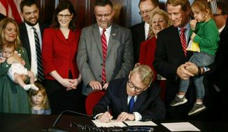 FILE - In this April 11, 2019 file photo, Gov. Mike DeWine speaks before signing a bill imposing one of the nation's toughest abortion restrictions in Columbus, Ohio.  A federal judge has blocked part of an Ohio law that bans the abortion method of dilation and evacuation in most cases. Senior U.S. District Judge Michael Barrett in Cincinnati ordered the state Thursday, April 18 not to bring criminal charges against doctors who perform the procedure until the case can be litigated.  The ruling comes a week after a separate heartbeat abortion ban was signed into Ohio law. (Fred Squillante/The Columbus Dispatch via AP)