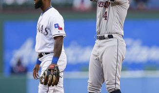 Texas Rangers second baseman Danny Santana, left, looks away as Houston Astros' George Springer (4) celebrates a double during the first inning of a baseball game Friday, April 19, 2019, in Arlington, Texas. (AP Photo/Brandon Wade)