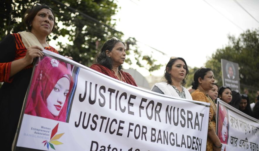 Protesters hold placards and gather to demand justice for an 18-year-old woman who was killed after she was set on fire for refusing to drop sexual harassment charges against her Islamic school's principal, in Dhaka, Bangladesh, Friday, April 19, 2019. (AP Photo/Mahmud Hossain Opu)